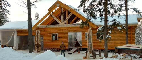 Kaleb outside log cabin before stain on entry Whitefish columbia falls montana